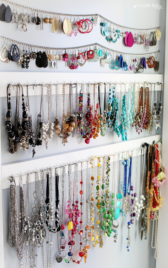 Earrings and necklaces hanging on chains and wall hooks