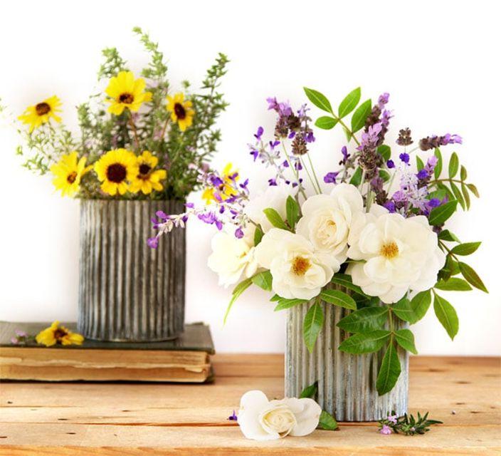 Dos flores en floreros sobre una mesa de madera