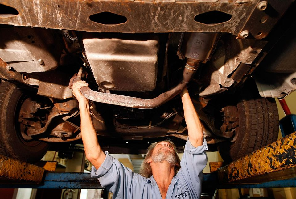 A mechanic replaces a stolen catalytic converter