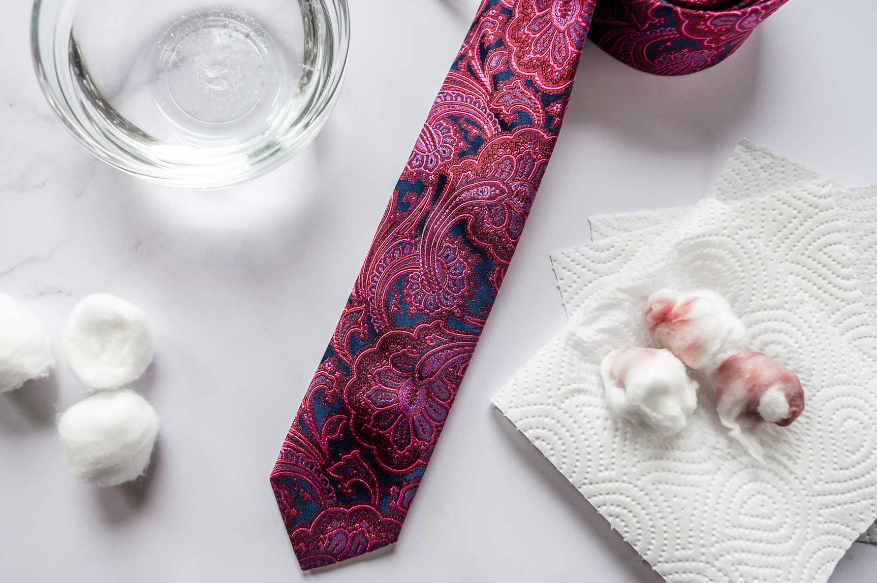 A tie next to cotton balls, napkins, and club soda