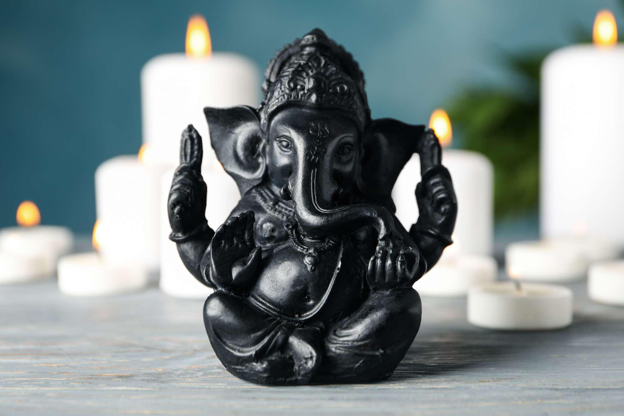 Hindu god Ganesha on white wooden table. Candles on background