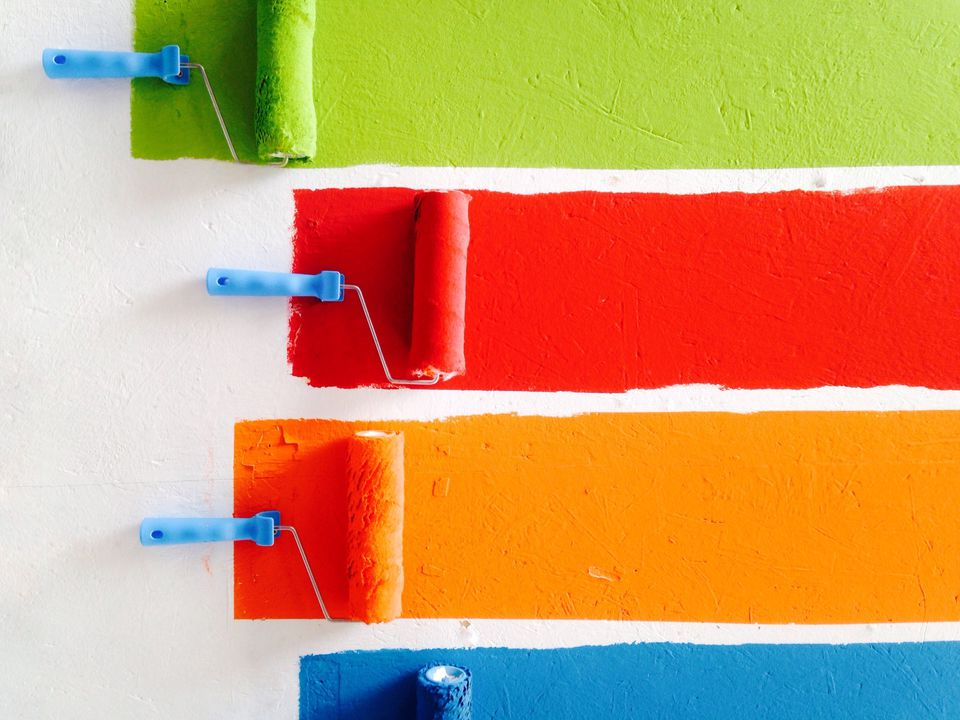 Four paint roller brushes rolling across a white wall in green, red, orange, and blue