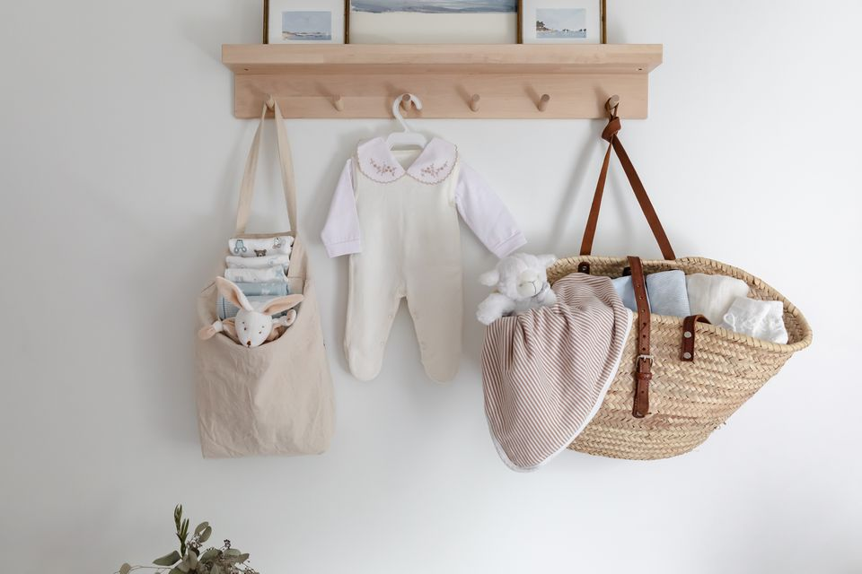 Baby clothes and handbags with toys hanging on wall shelf