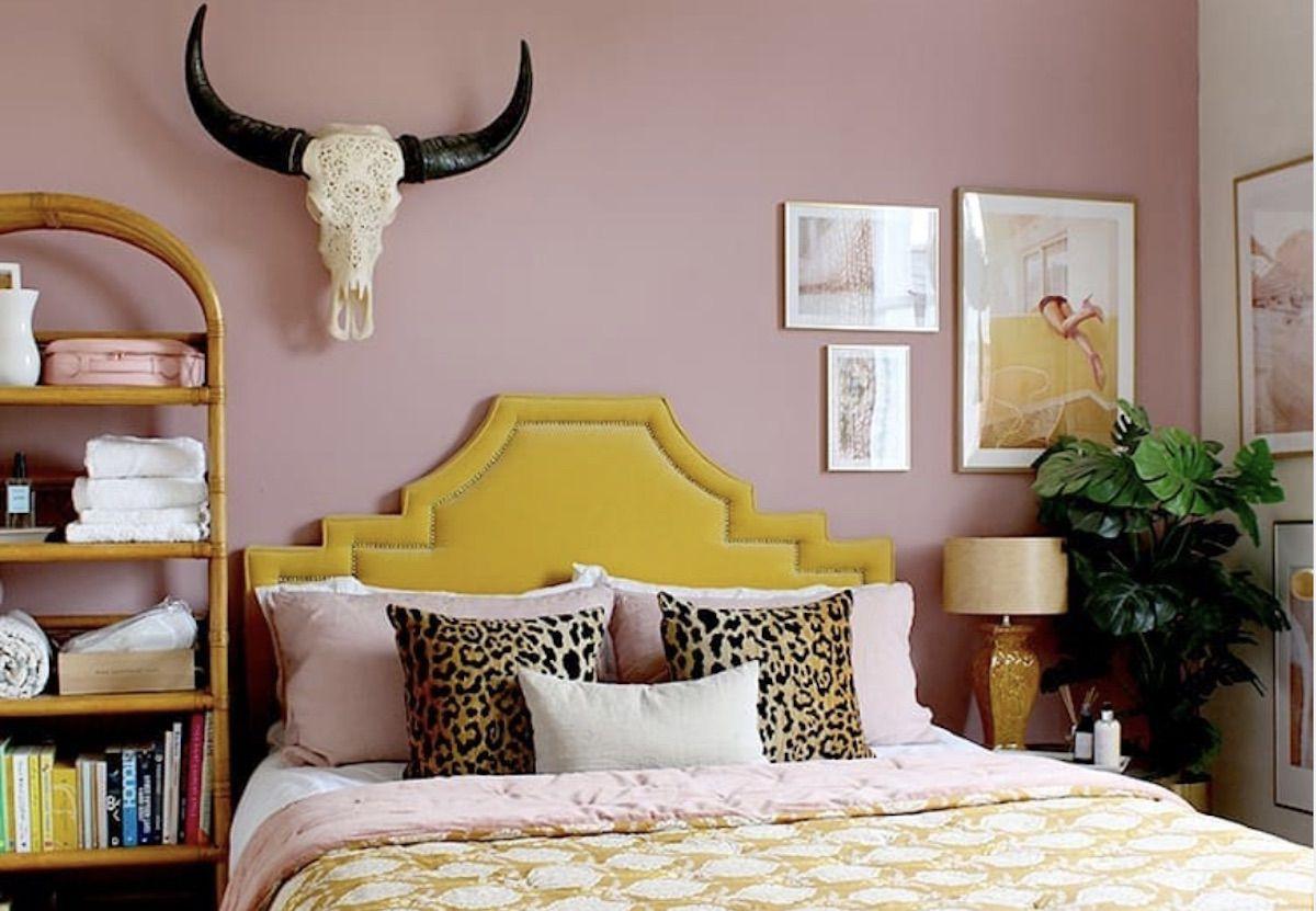 boho western bedroom with pink walls, yellow headboard
