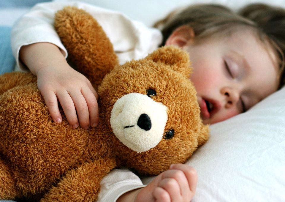 A boy sleeping with a teddy bear
