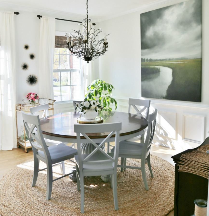 Coastal-inspired dining room with white walls and round farmhouse table.
