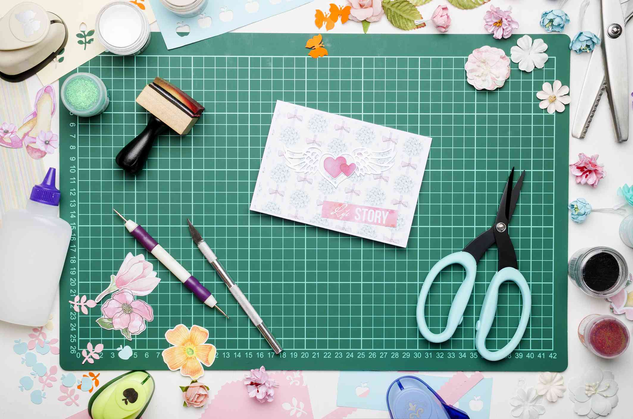 greeting card on green cutting mat, scrapbooking tools and materials