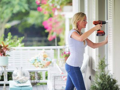 Woman using impact driver on porch