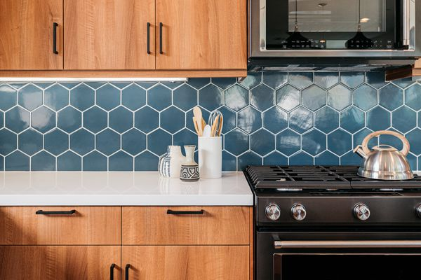 Blue geometric adhesive tile mat backsplash in kitchen with wood cabinets and black appliances