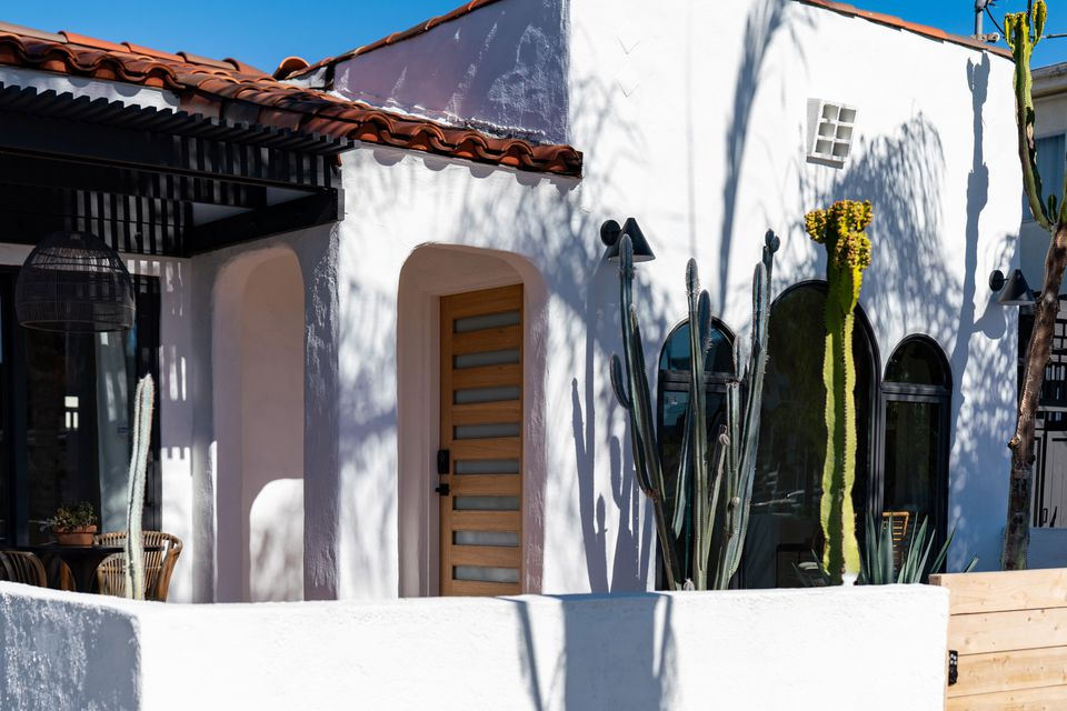White stucco painted house with tall cactus in front with sunlight