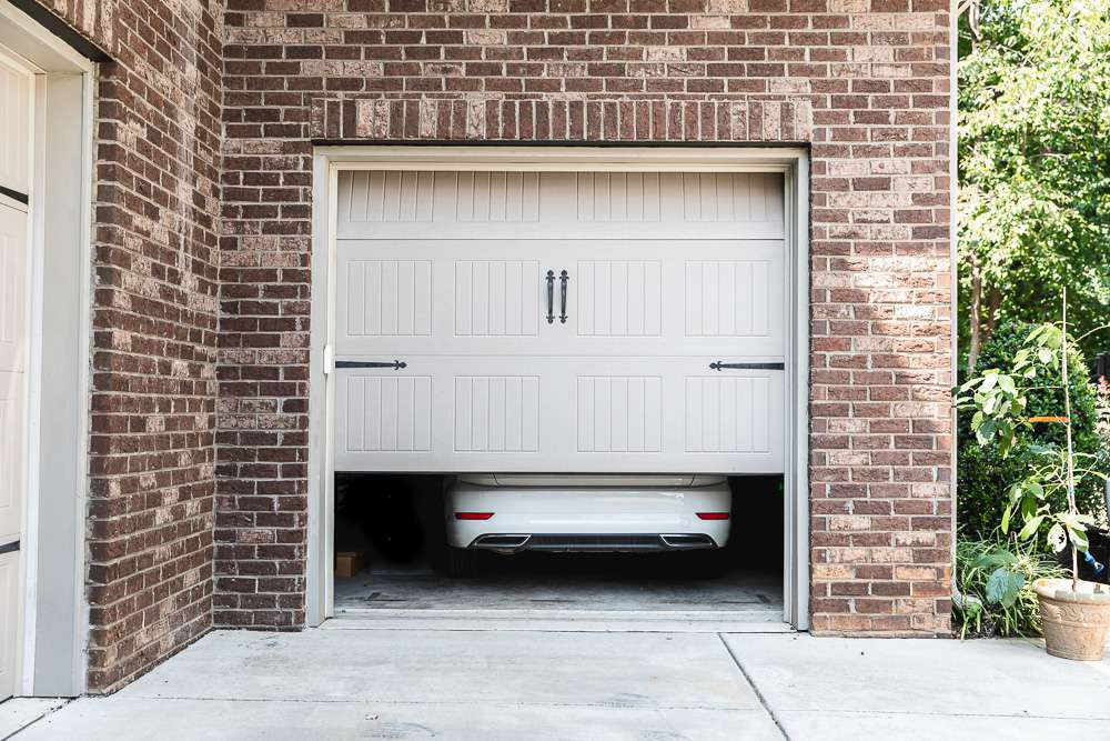 Tan garage door partially closed with white car inside