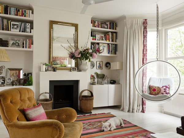 Living room with a bay window, built-in bookshelves, an Aztec-style rug, a yellow velvet armchair, and a lounging white dog.