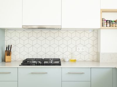 Small kitchen with white upper cabinets and mint green lower cabinets, plus geometric backsplash.