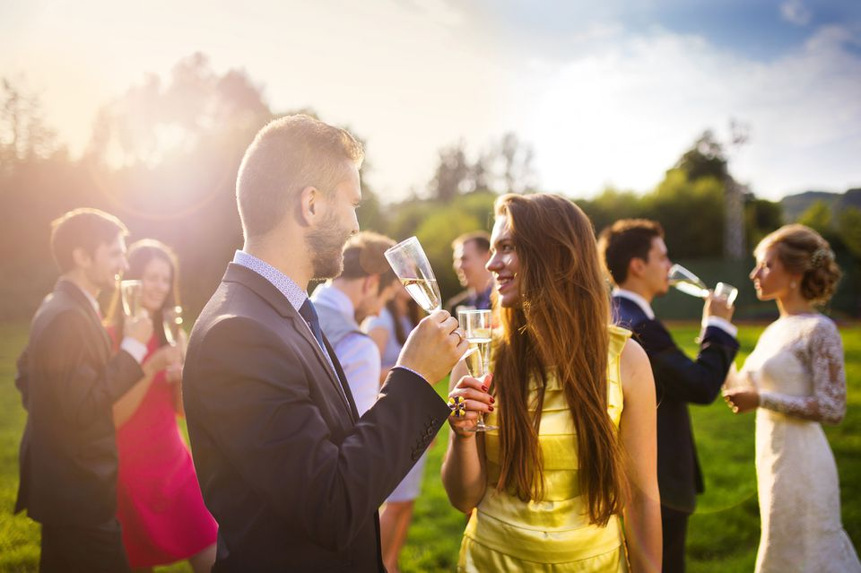 Wedding guests clinking glasses at wedding