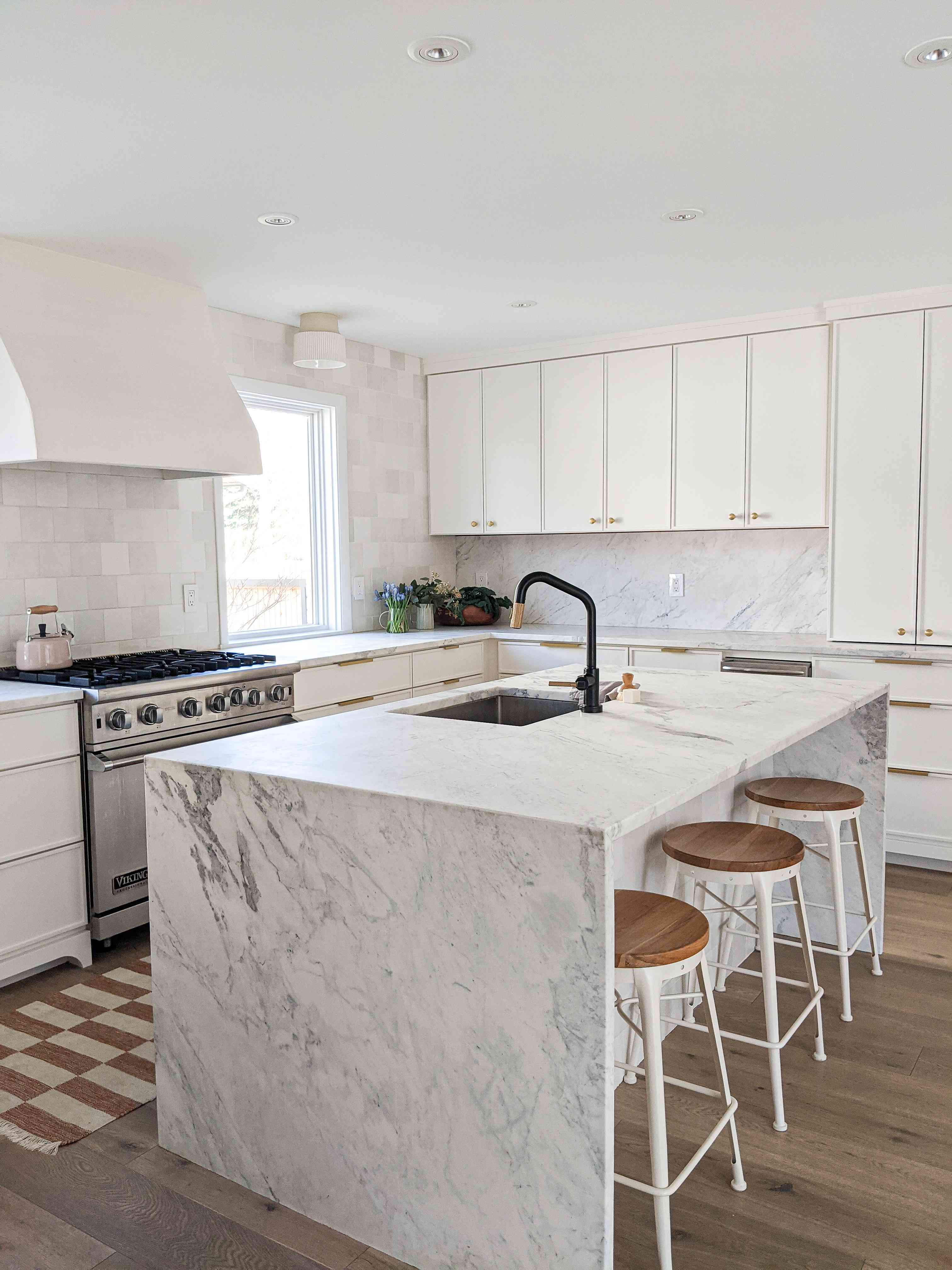 The kitchen in the Shaker Heights home of Molly & Fritz features a marble waterfall island and black hardware