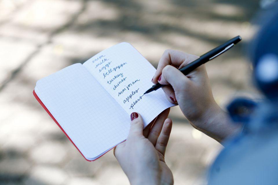 A woman writes a grocery list