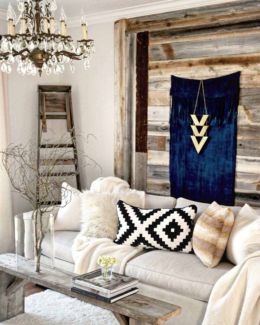 A black-and-white Ikea pillow and gold, metal chevrons hung over a wall tapestry