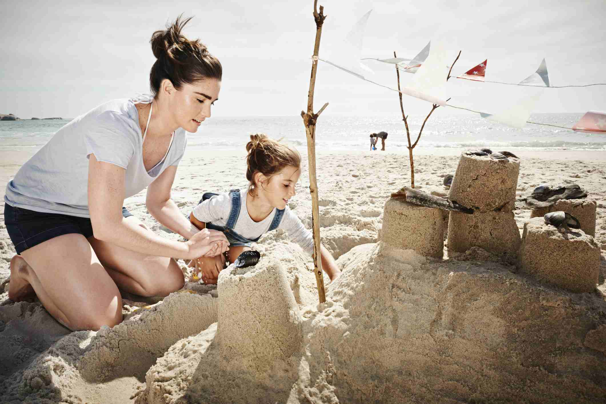 Mom and daughter building a sandcastle on vacation