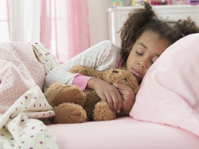 Young girl sleeping with teddy bear