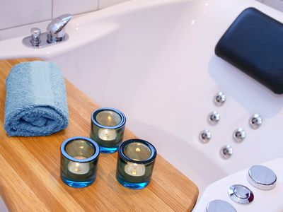 Jetted bathtub with candles, pillow, and towel