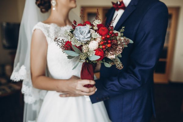 bride and groom holding bouquet with red roses and succulents. gorgeous wedding couple with rustic flowers. boho newlyweds