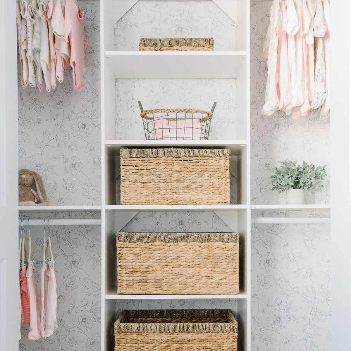nursery closet with multiple rods to hang clothes and storage shelves with wicker baskets for others