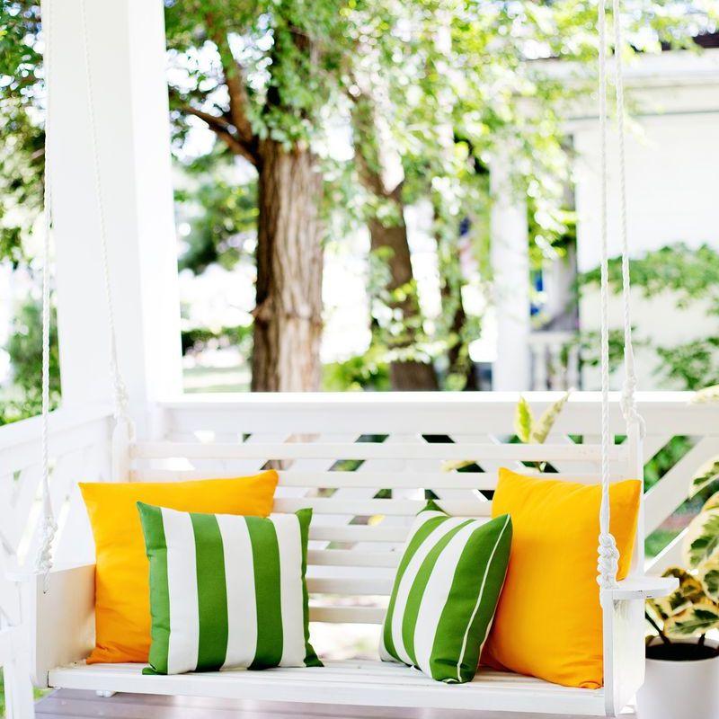 Una foto de un columpio con porche con cojines verdes y amarillos