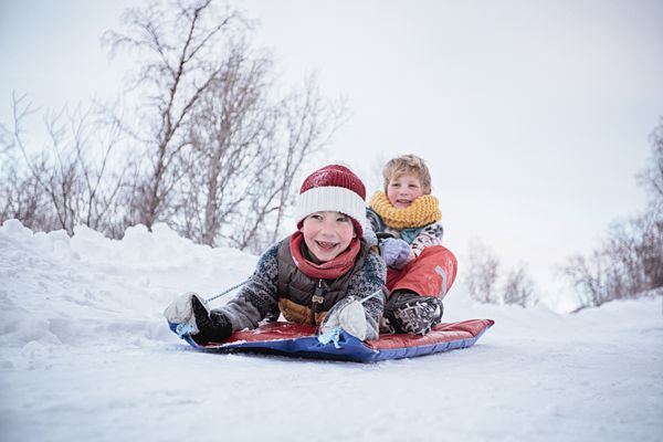 Low angle view of two brothers on toboggan on snow covered hill, Hemavan,Sweden