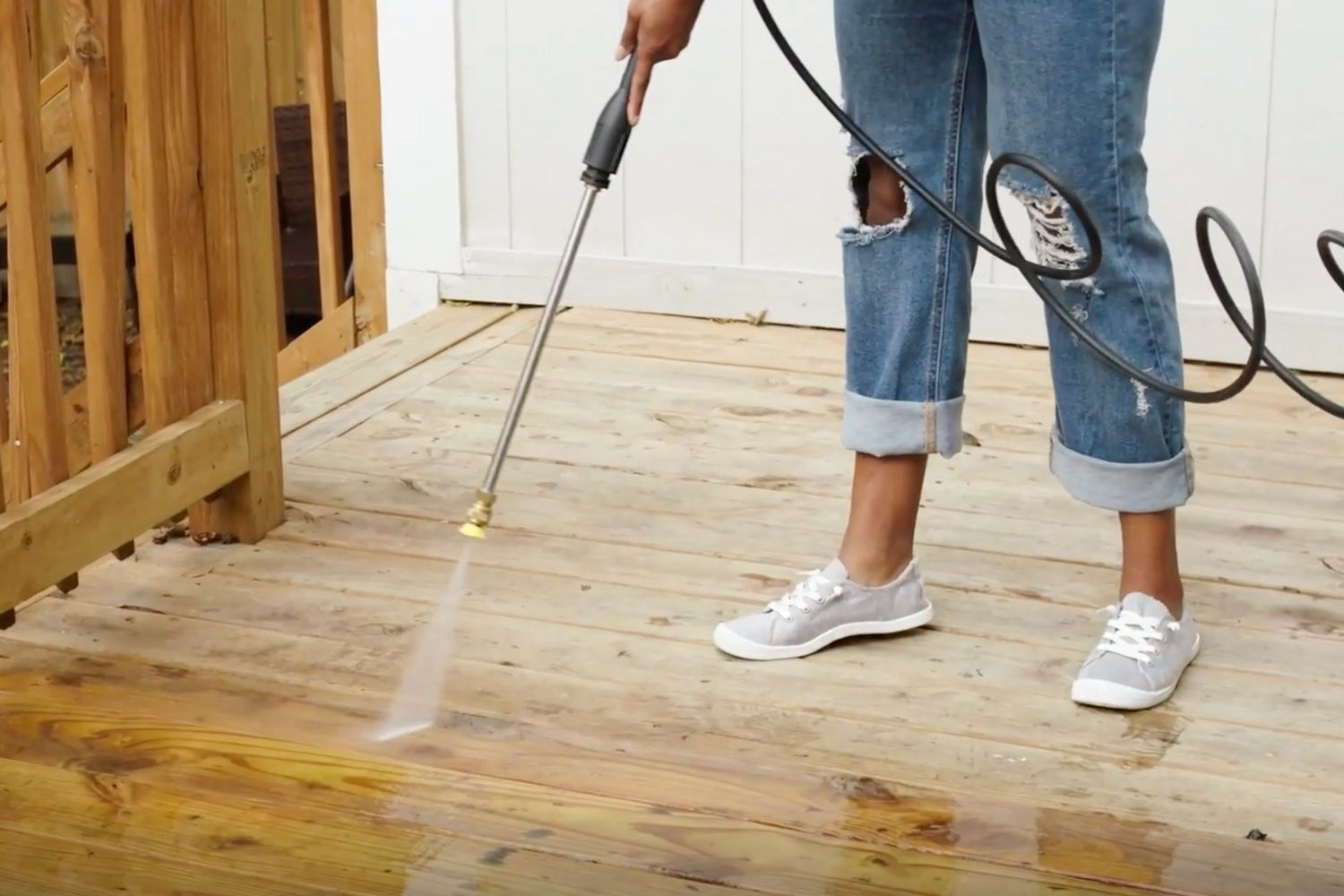 person power washing a wood deck