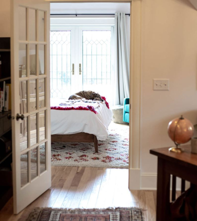 Attic bedroom with french doors and dog laying on bed.