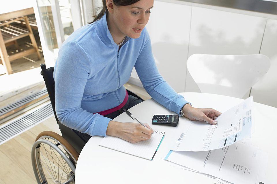 Woman in wheelchair calculating bills at kitchen table