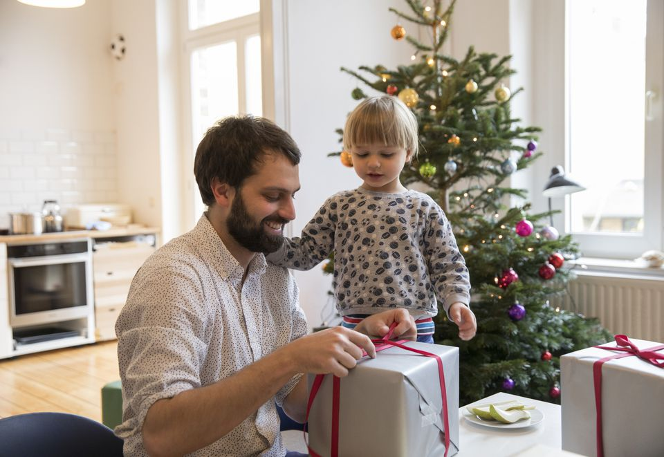 Cheerful father and toddler son wrapping christmas presents while sitting at table in front of christmas tree