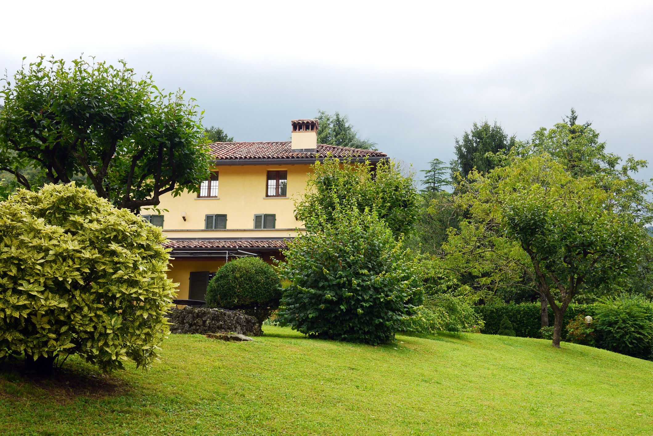 Los arbustos y árboles le dan privacidad a este hogar italiano.