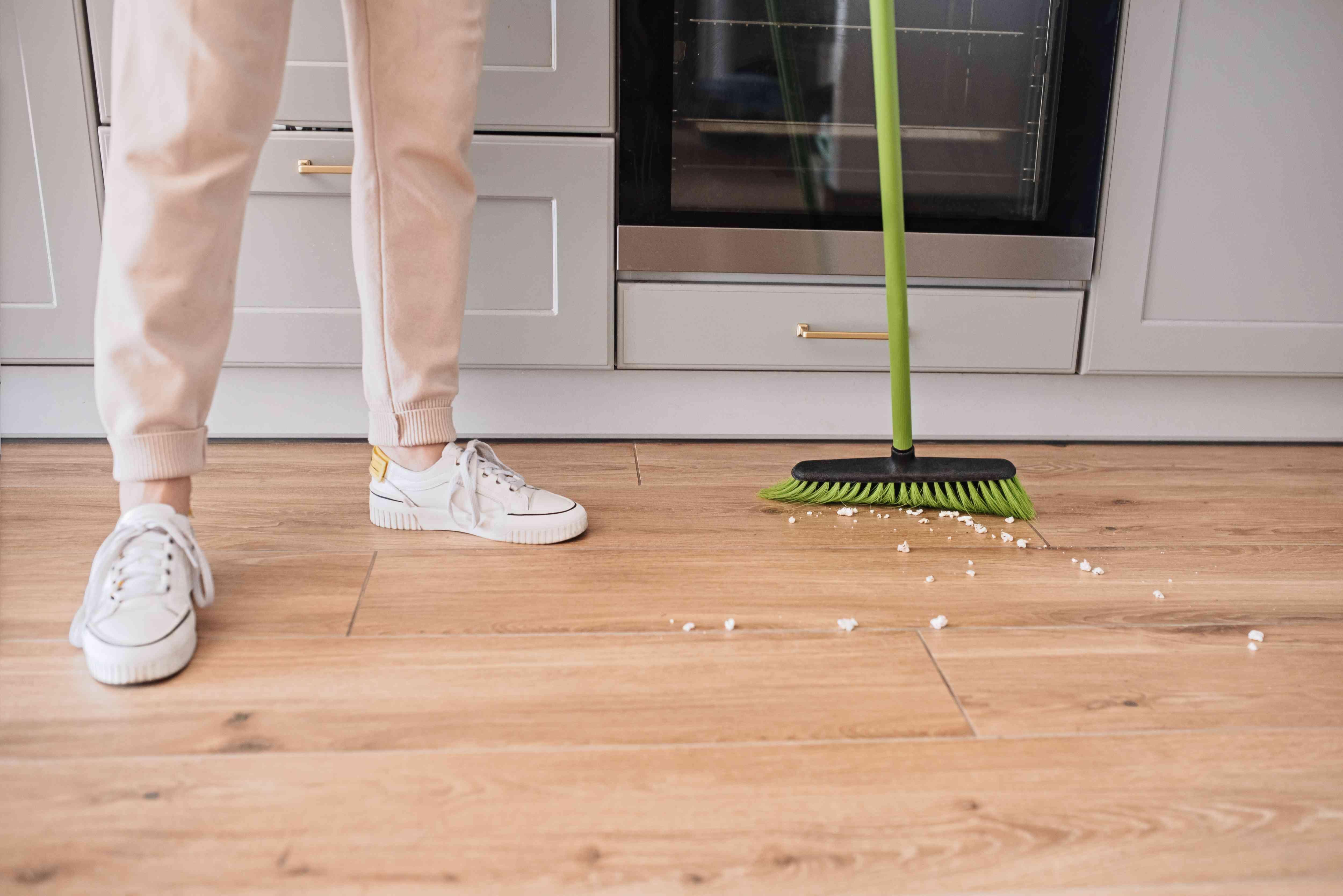 Green broom sweeping white debris on wooden floor