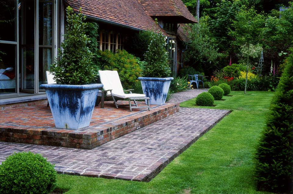 Brick patio between house and lawn with basket-weave pattern.