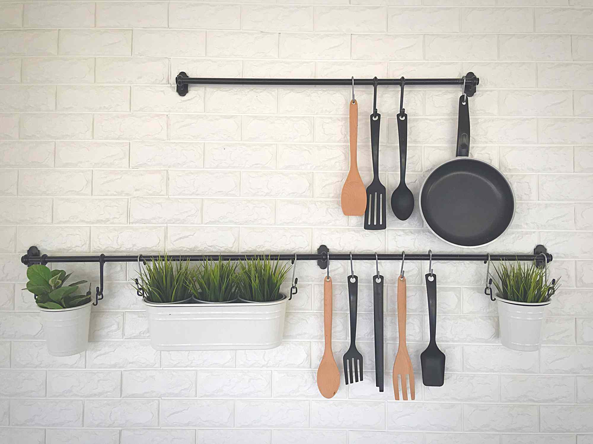 Kitchen utensils and potted greenery hanging from towel rods.