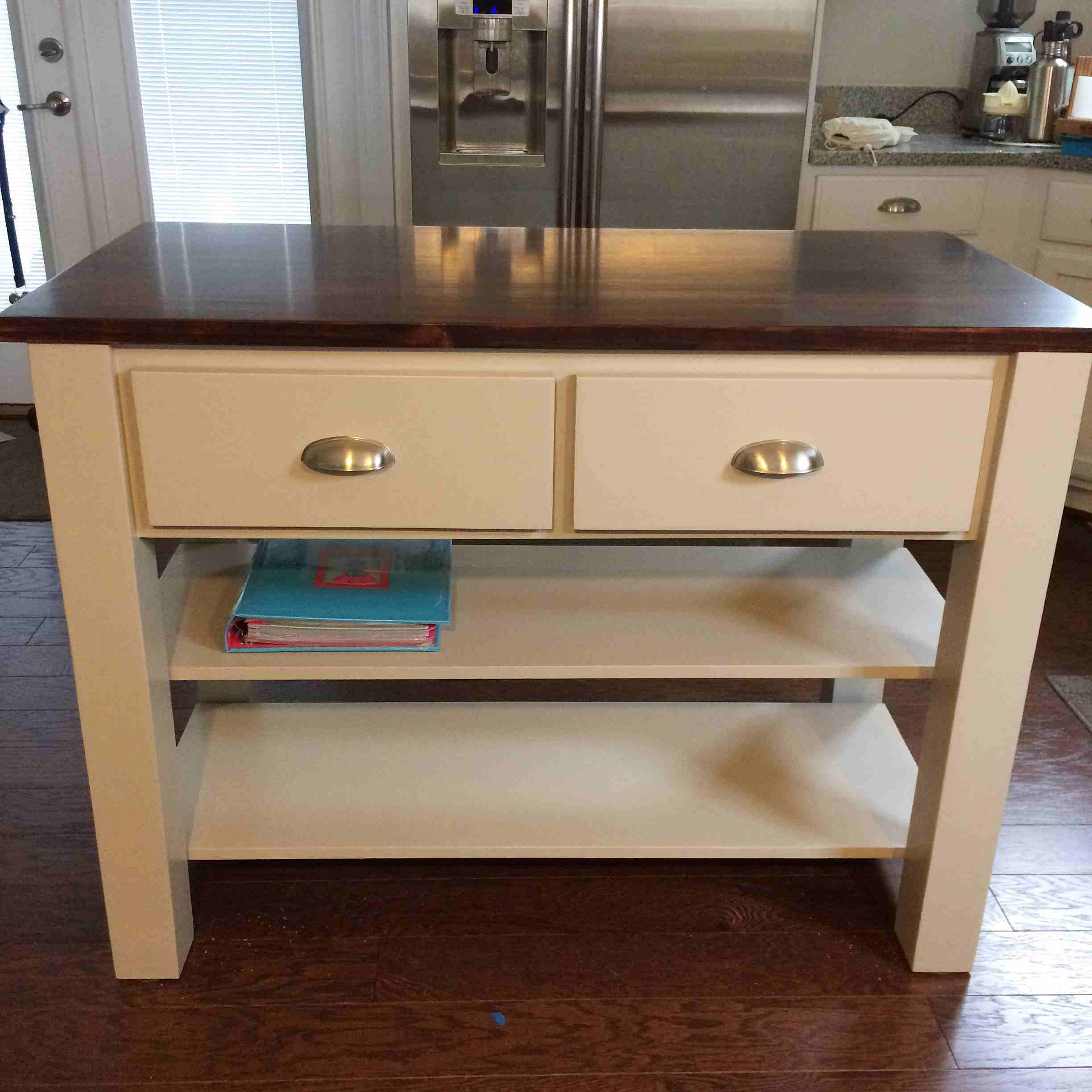 A Kitchen Island With Two Drawers And Shelves