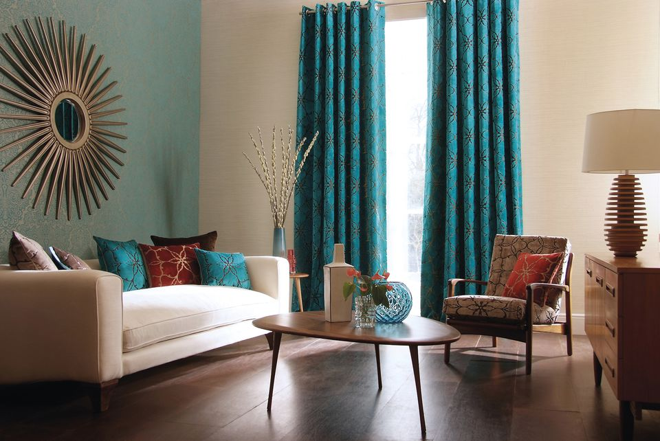 Contemporary living room with long blue curtains over window and blue accent wall behind white couch.