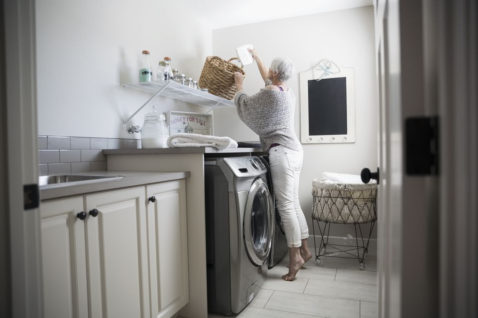 Woman reaching for basket in laundry room