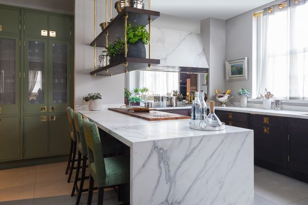 White kitchen features marble island and walls, plus green built-in cabinetry and stools