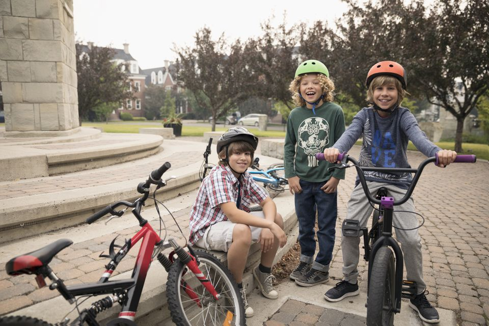 Portrait smiling boy friends with bicycles in park