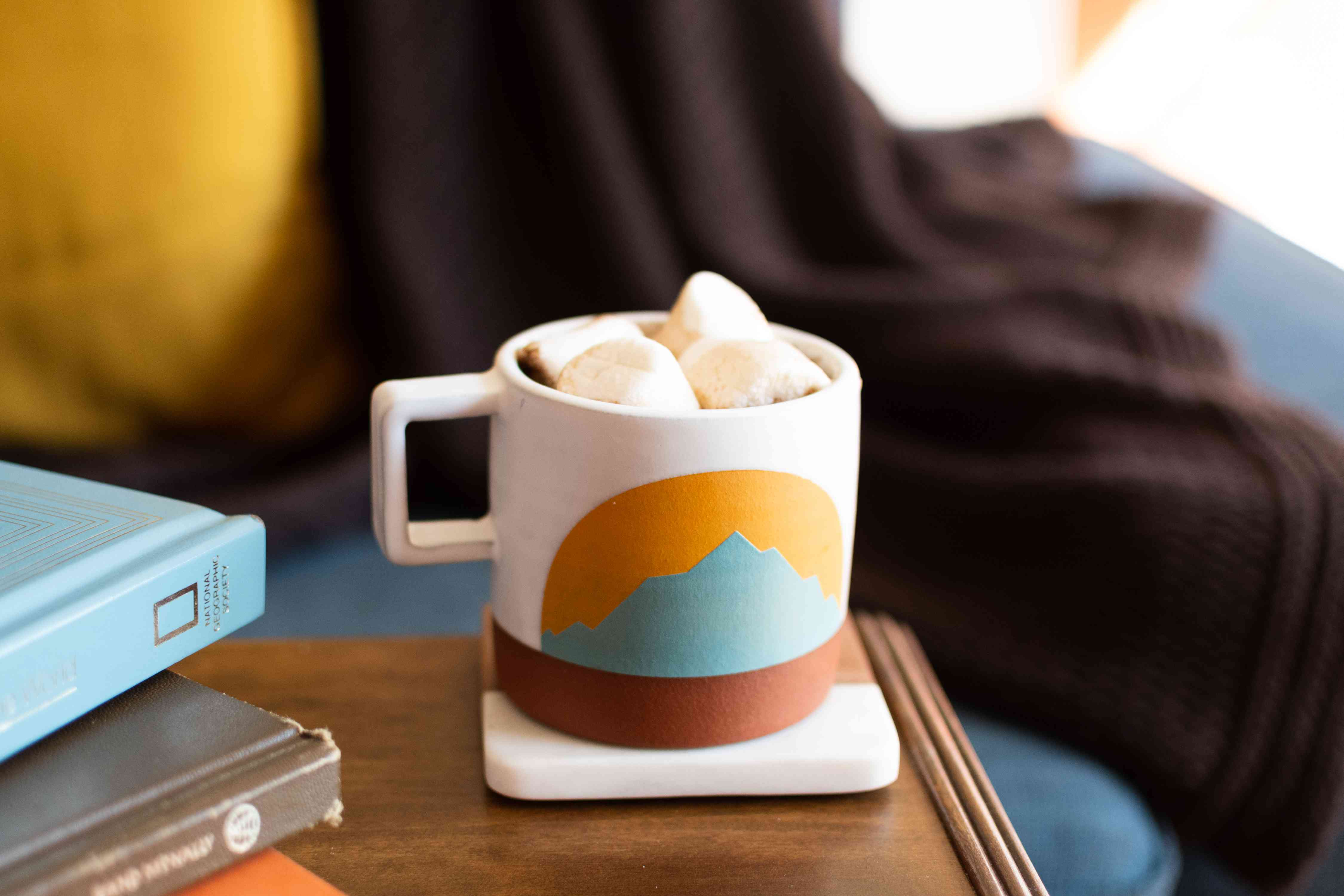 Marshmallows on top of hot beverage in painted mug with mountain-scape closeup