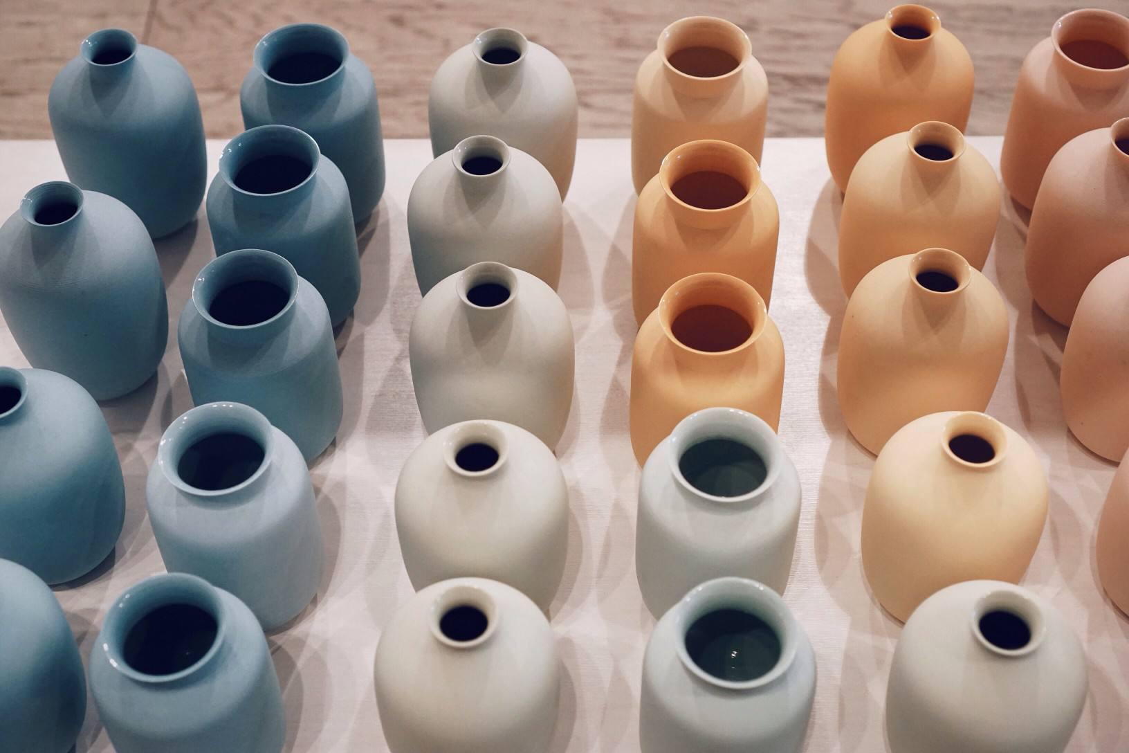 Arrangement of dozens of colorful ceramic vases.