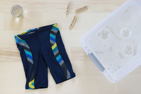 Swimsuit next to plastic bu with cleaning solution, clothing pins and detergent