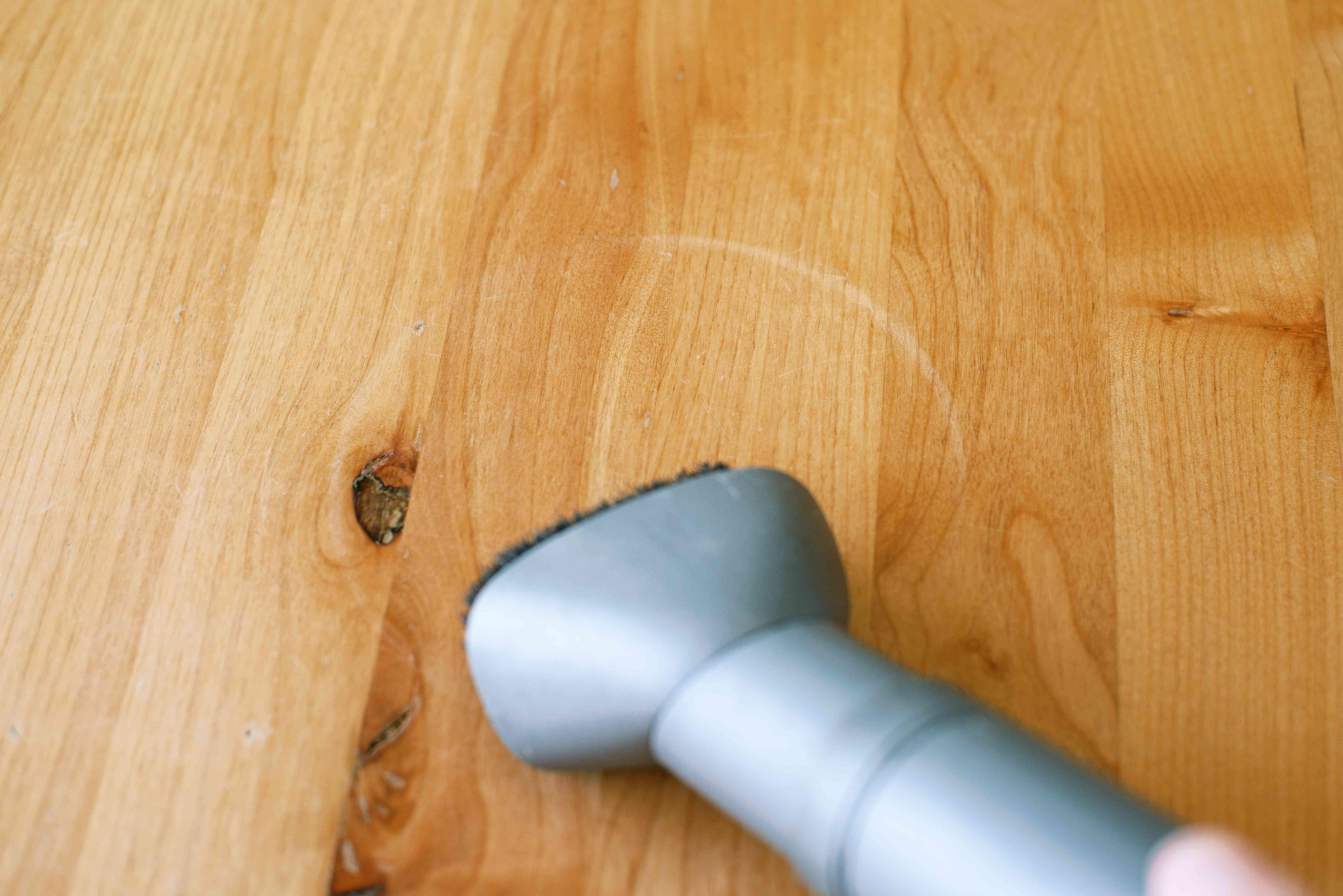 White water ring on wood floor being vacuumed