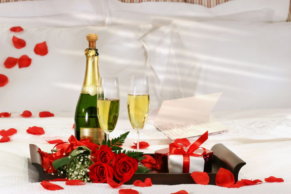 Champagne, roses, and gift waiting on romantic bed