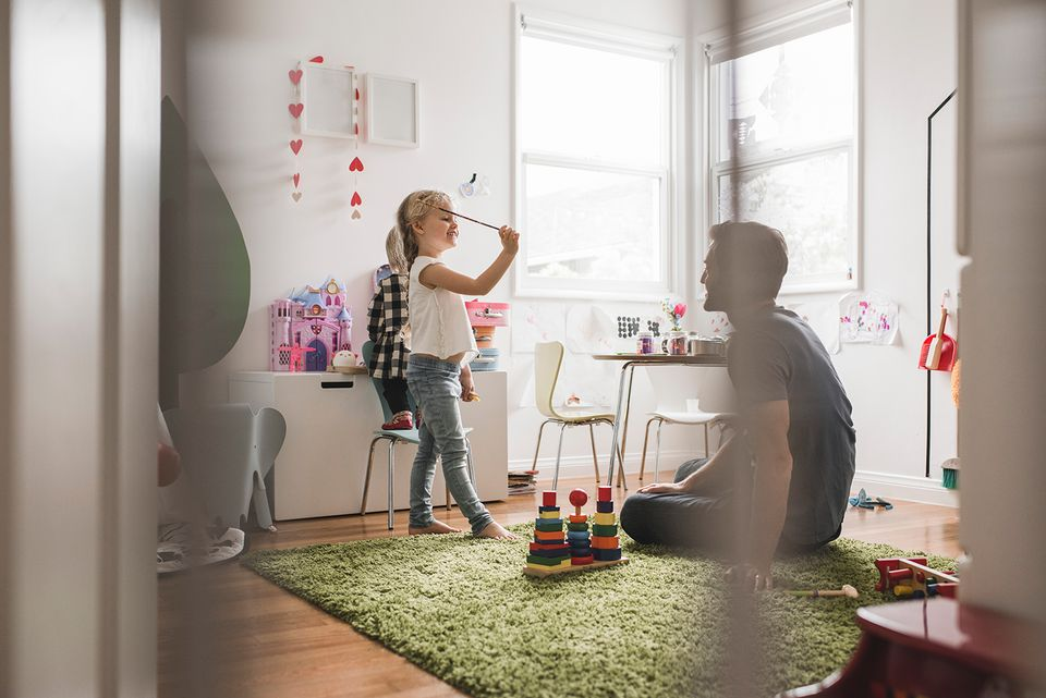 Father looking at daughters playing with toy in playroom at home