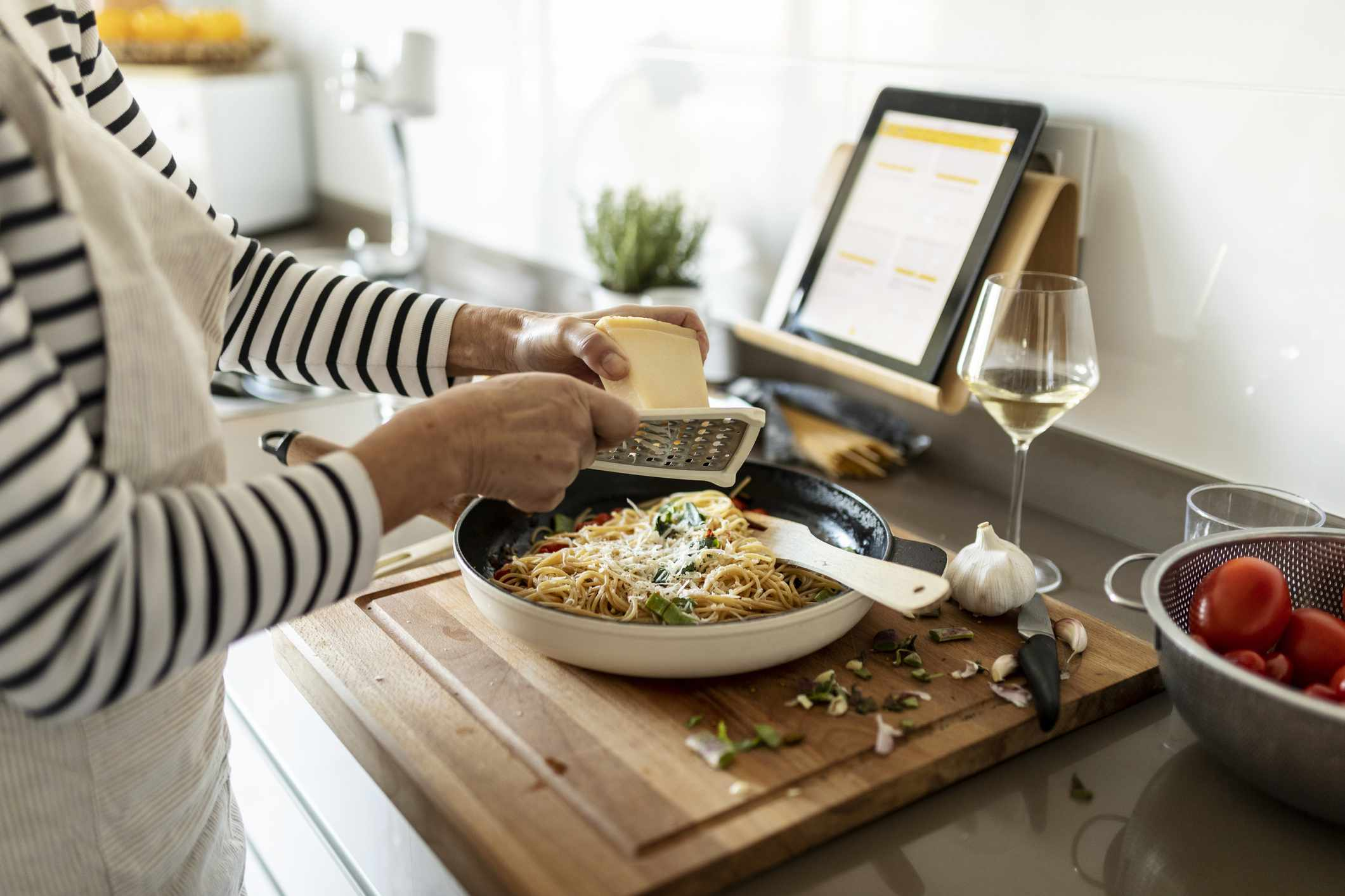 A woman grating cheese and cooking.