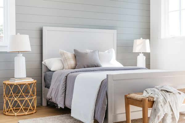 Farmhouse-style bedroom with light gray and white decor accents next to wooded bench and night stands