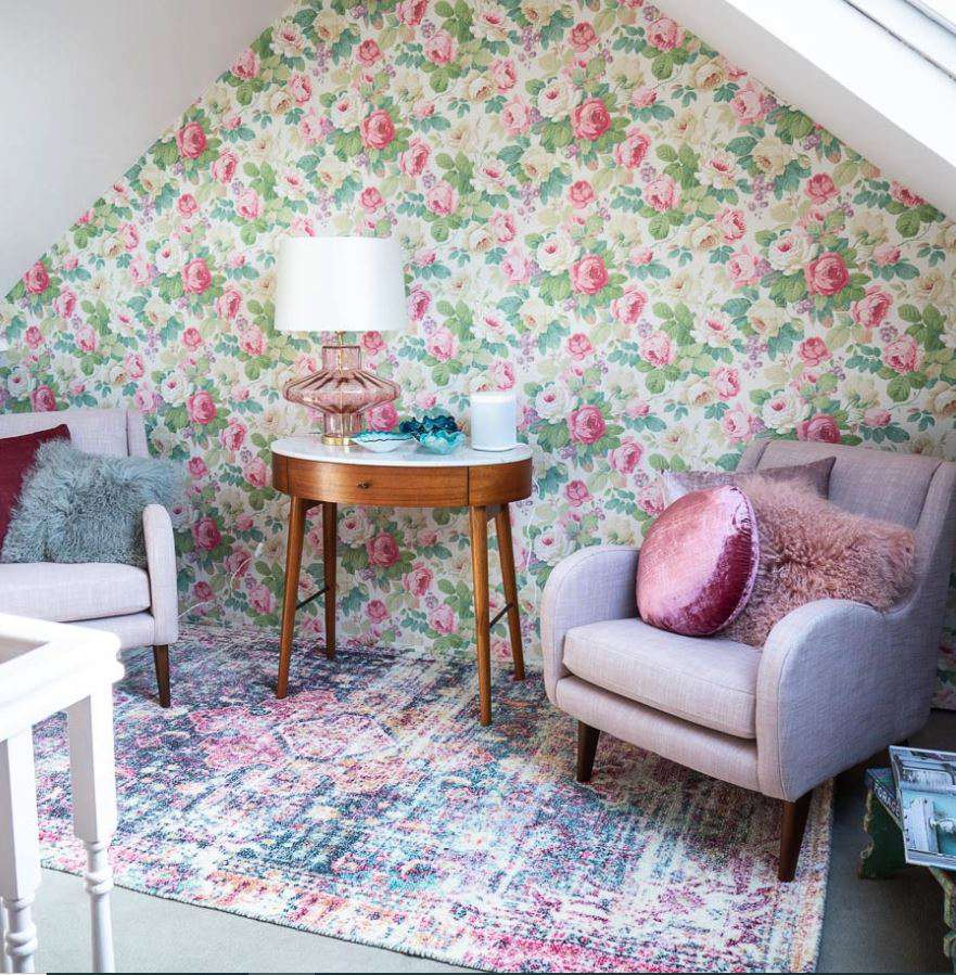 Updated attic space with floral wallpaper accent wall.